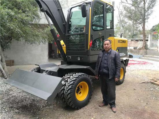 老板和新提的轮式挖掘机合影